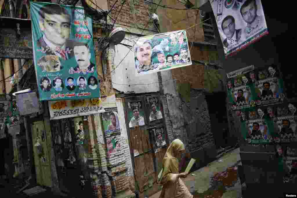A girl walks in the old part of Lahore decorated with election posters. (Reuters/Damir Sagolj)
