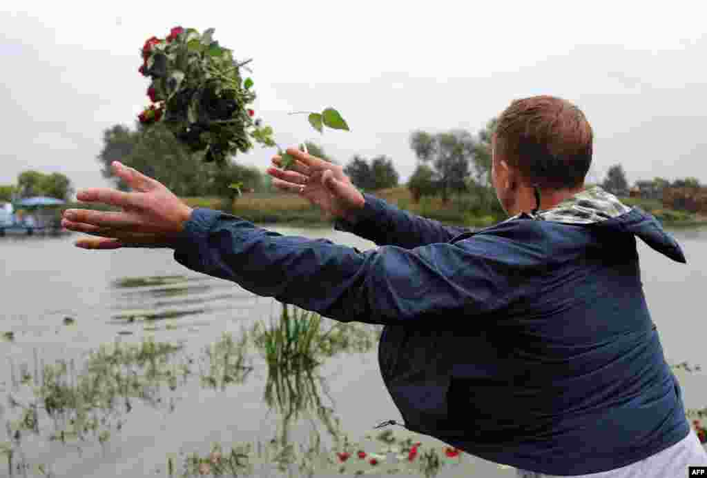 A man throws flowers at the plane crash site beside the Tunoshna River.