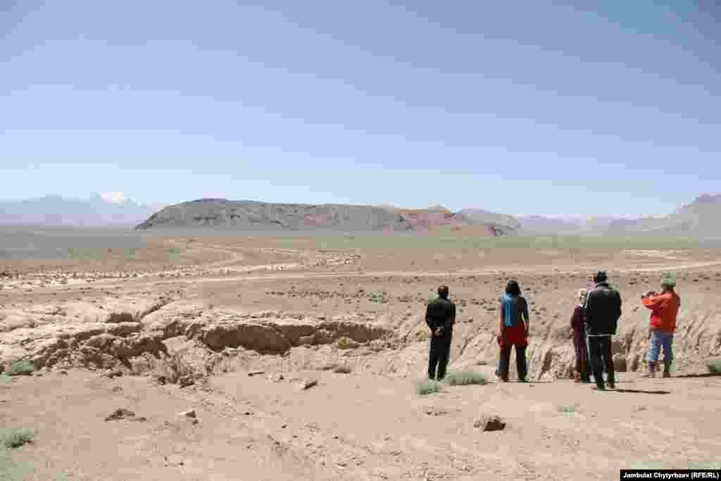 Locals and tourists look at a crater created by a meteorite some 50 years ago.