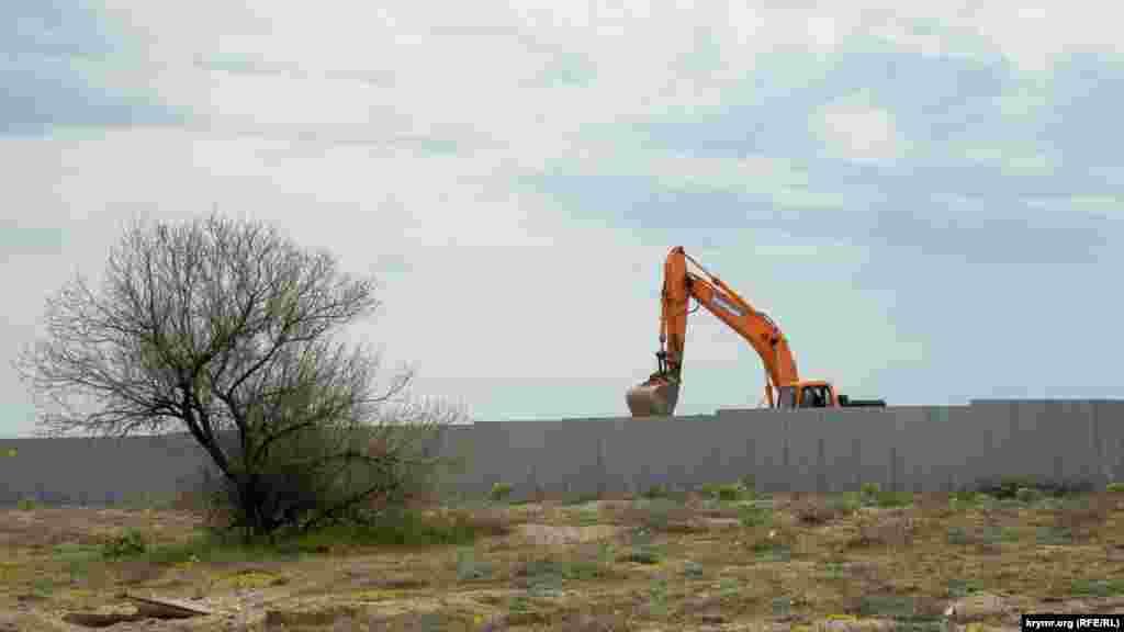 А другой экскаватор что-то потихоньку ковыряет за строительным забором