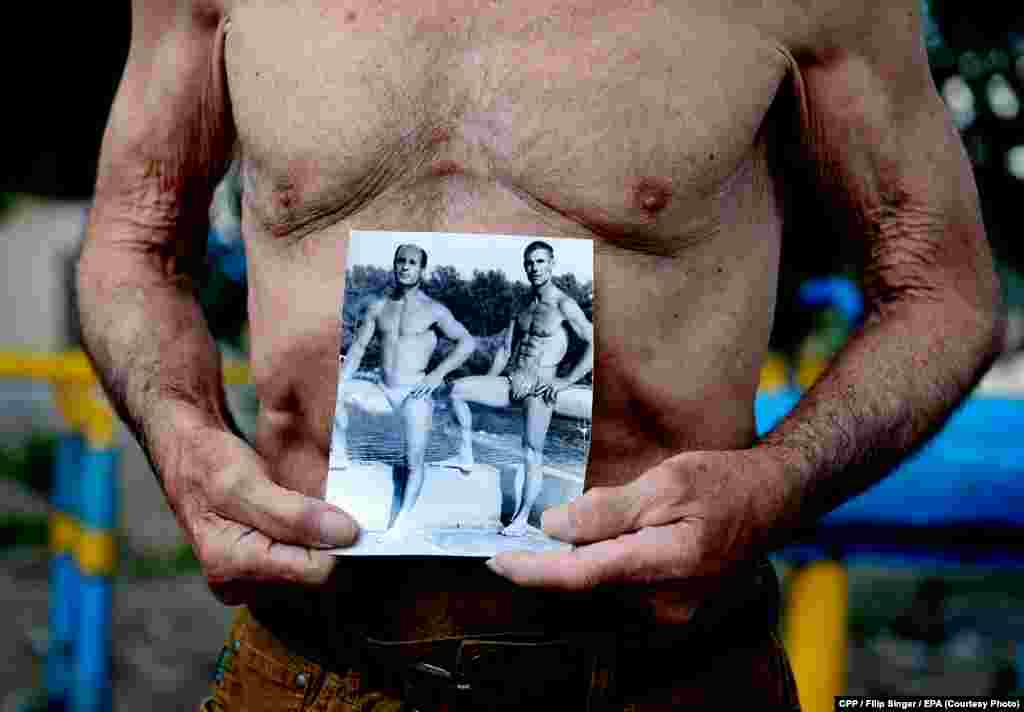 Second Prize, Sport:An 81-year-old former Soviet athlete shows an old picture of himself at the Kachalka outdoor fitness center in Kyiv, Ukraine. (epa/Filip Singer)