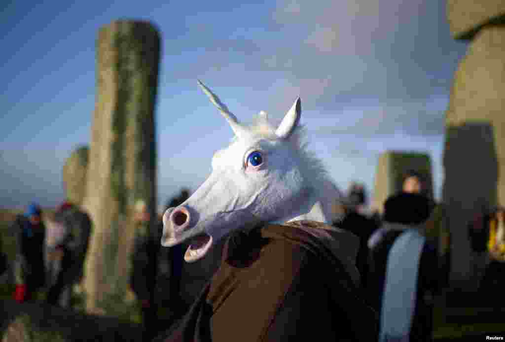 A reveler, dressed as a unicorn, celebrates the sunrise during the winter solstice at Stonehenge on Salisbury Plain in southern England. (Reuters/Kieran Doherty)