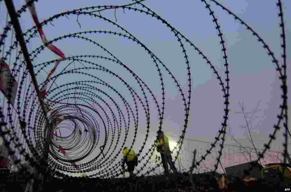 Рабочыя замяраюць амаль дабудаваны ўчастак агароджы даўжынёй 3.7 кілямэтра на мяжы паміж Аўстрыяй і Славэніяй. (AFP/Joe Klamar)