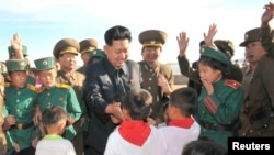 Disa fëmijë duke përshëndetur liderin verikorean Kim Jong Un.