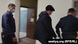 Обвиняемого в коррупции бывшего начальника управления здравоохранения Болатбека Каюпова выводят из зала суда. Уральск, 2 февраля 2021 года.