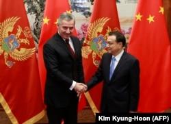 Milo Djukanovic (kiri), yang saat itu menjadi perdana menteri Montenegro, berjabat tangan dengan Perdana Menteri China Li Keqiang selama pertemuan mereka di Aula Besar Rakyat di Beijing pada November 2015.