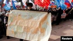 Мужчина держит карту Советского Союза во время акции протеста в российском городе Красноярск. 13 марта 2014 года.