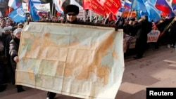 A man holds a map of the Soviet Union during a rally to support Russian-speakers living in Crimea and Ukraine, in the center of the Siberian city of Krasnoyarsk.