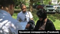 Співробітник російської прокуратури вручає застереження адвокату Еміне Авамілєвій