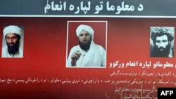 A billboard with photos of Osama bin Laden (left), Adam Gadhan (center), and Mullah Mohammad Omar, posted in a Kabul park, asks for information regarding the whereabouts of the Al-Qaeda fugitives.