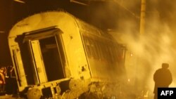 Workers inspect a damaged railway carriage