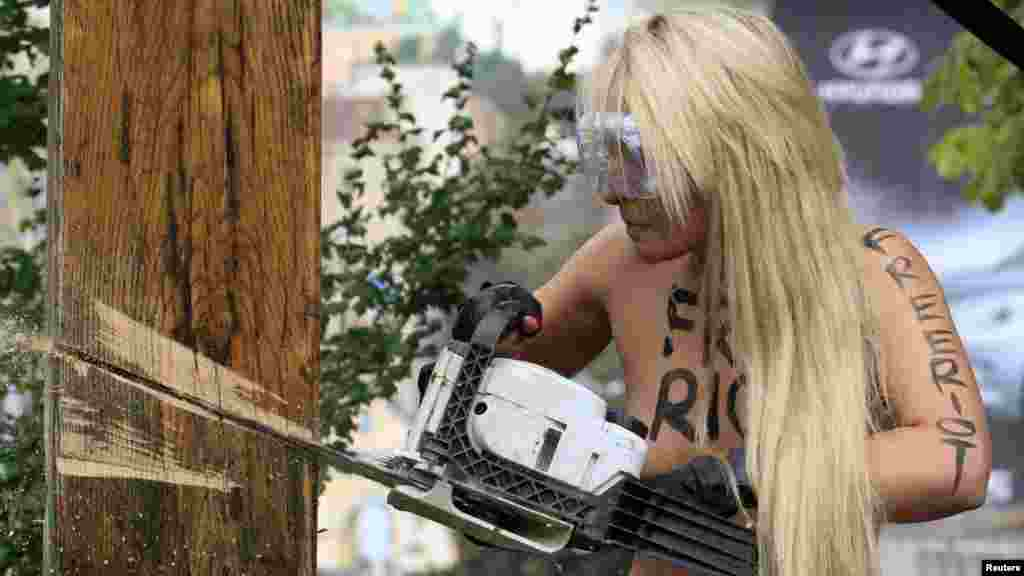 An activist from the women's rights group Femen uses a chainsaw to cut down a cross erected in memory of victims of political repression under Stalin in Kyiv to protest the Pussy Riot case.
