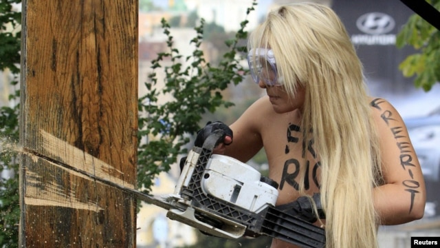 A Femen activist uses a chainsaw to cut down an Orthodox cross in Kyiv on August 17.