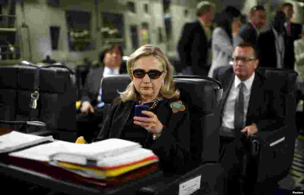 U.S. Secretary of State Hillary Clinton checks messages as she flies to Tripoli, Libya, on a military plane in October 2011. The following year, Libya became the site of a critical challenge in Clinton's time in office after four Americans were killed in an attack on the U.S. diplomatic mission in Benghazi. Clinton faced criticism over her handling of the attack, although an inquiry found she was not at fault.