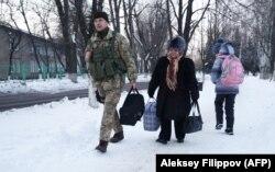 Український військовий допомагає жительці Авдіївки, січень 2017-го