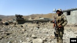 FILE: Afghan security official stands guard at the scene of a suicide bomb attack in Logar August 2015.