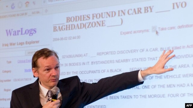 The founder of the WikiLeaks website, Julian Assange, displays a page from the released documents to journalists in London on October 23.