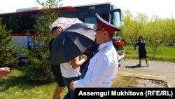 Неизвестные в присутствии полицейских закрывают видеокамеру Азаттыка зонтами, мешая вести съемку. Нур-Султан, 9 мая 2019 года.