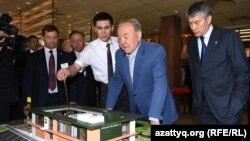 Қазақстан президенті Нұрсұлтан Назарбаев (ортада) McDonald's мейрамханасының макетіне қарап тұр. Оң жақта - бизнесмен Қайрат Боранбаев. Астана, 5 наурыз 2016 жыл.