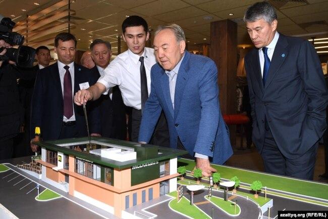 Президент Казахстана Нурсултан Назарбаев (в центре) рассматривает макет ресторана McDonalds. Слева от него стоит Кайрат Боранбаев. Астана, 5 марта 2016 года.