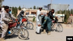 An Afghan security official checks people at a checkpost in Helmand.