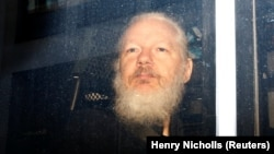 WikiLeaks founder Julian Assange is seen in a police van after his arrest by British police in London on April 11