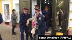 Полиция задерживает Бакизу Халелову, участницу митинга с требованием «освободить политзаключенных». Уральск, 10 мая 2018 года.