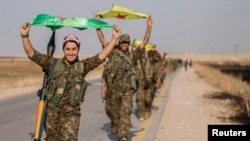 Kurdish fighters celebrate taking control of an area in Syria's Raqqa region last year.