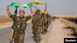 مقاتلون كرد يحملون أعلام أحزابهم في تل أبيض