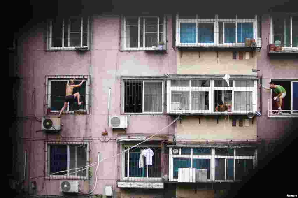 A man (left) climbs outside a window with a knife as his mother (center) and a plainclothes policeman look on, in Anshan, Liaoning Province, China. The man held his mother captive in his apartment before climbing out of the window and threatening to cut himself. After several hours, he was controlled by police who managed to enter the house from another window with the help of his mother. (Reuters)