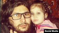 "An image from a posting by a Chechen militant of Islamic State's Chechen faction, Katibat al-Aqsa, who calls himself Abu Hamza but previously was known as Ilyas Deniyev, with a child identified as ""Khadija,"" whose face has been pixelated to protect her identity."
