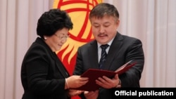Akmatbek Keldibekov (right), then the parliament speaker, consults with then-Kyrgyz President Roza Otunbaeva in November 2011.