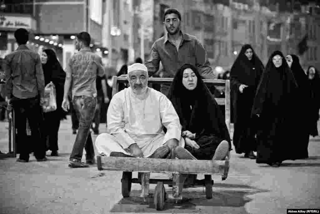 A father and daughter with limited mobility receive assistance while visiting holy Shi'ite sites in Karbala.