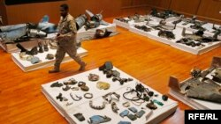 A Saudi military officer walks by what was described asa the remains of Iranian cruise missiles and drones used in an attack this weekend that targeted the heart of Saudi Arabia's oil industry, during a press conference by military spokesman Col. Turki al