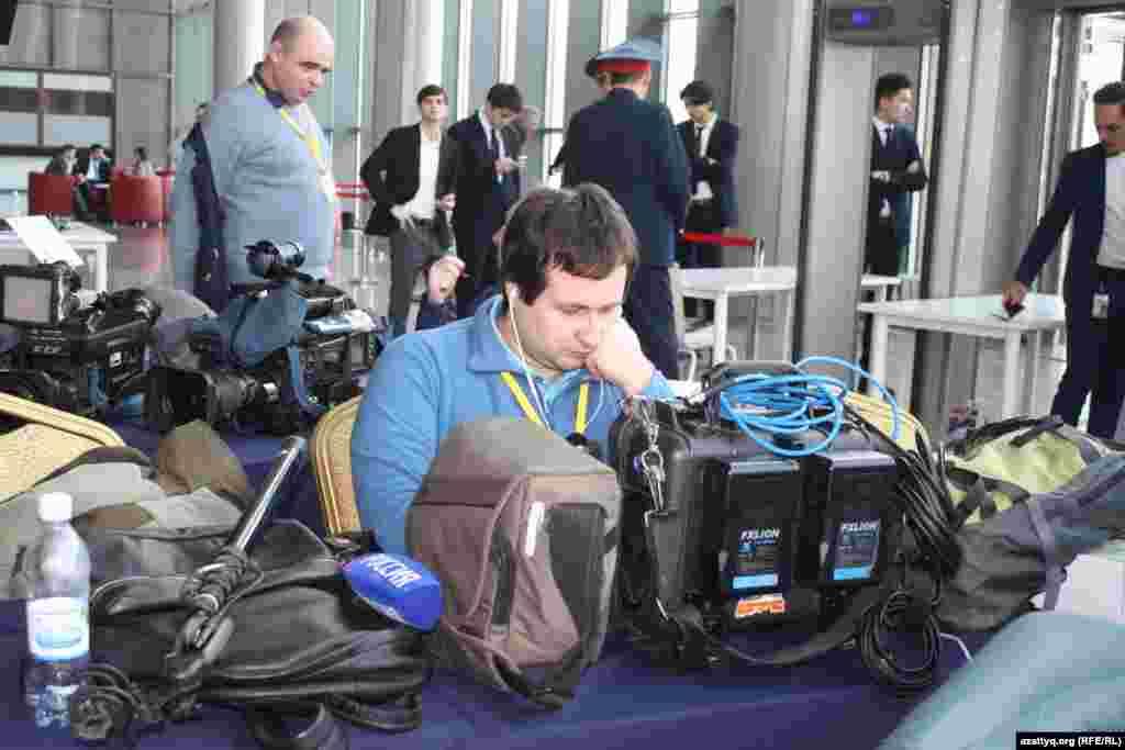 Российский журналист проверяет технику перед началом переговоров.