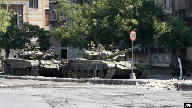 Syrian Army tanks are seen in the Al-Midan area of Damascus.