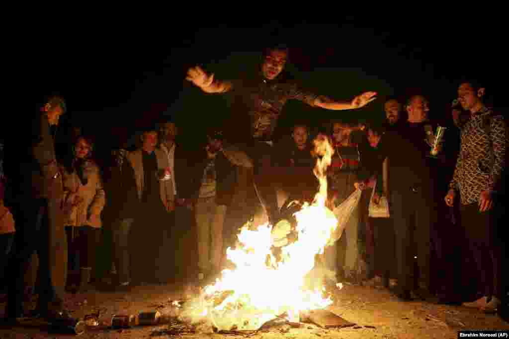 "An Iranian man jumps over a bonfire during a celebration, known as ""Chaharshanbe Souri,"" or Wednesday Feast. This celebration marks the eve of the last Wednesday of he solar Persian year, Tuesday, March,19,2019 in Tehran, Iran."