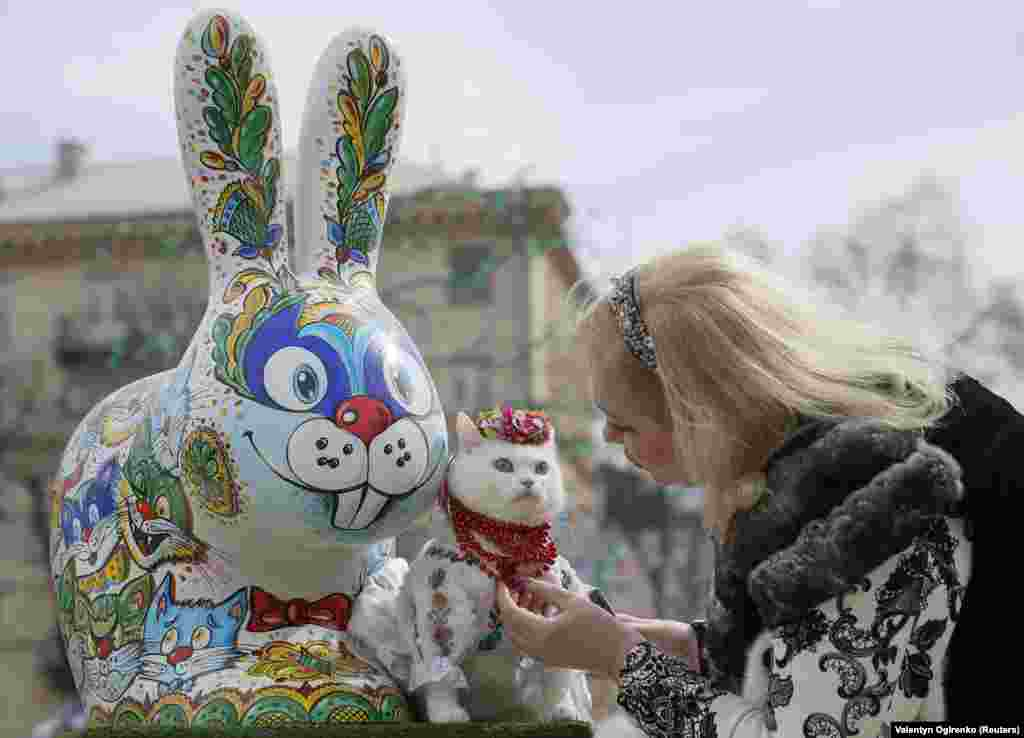 A woman dresses her cat before taking pictures near a painted Easter Bunny displayed in a square as part of Orthodox Easter celebrations in central Kyiv, Ukraine. (Reuters/Valentyn Ogirenko)