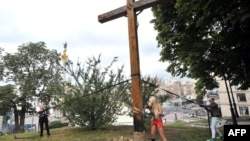 Femen activists use a chainsaw to cut down an Orthodox cross in Kyiv.