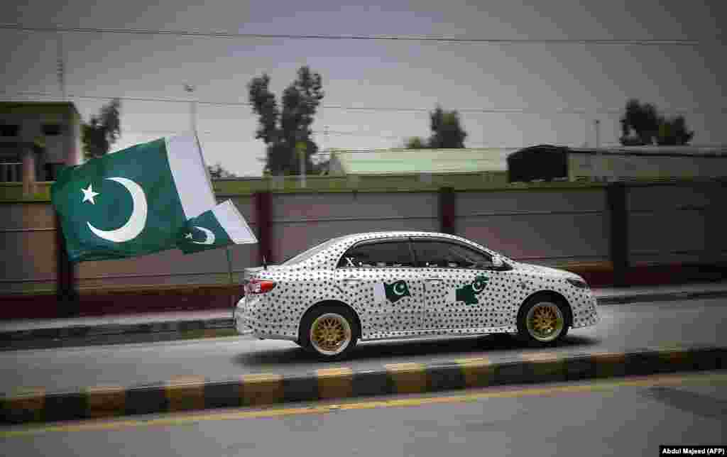 A Pakistani resident drives his car decorated with national flags to mark the country's Independence Day in Peshawar on August 14. (AFP/Abdul Majeed)
