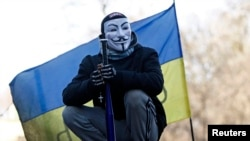 A Ukrainian antigovernment protester stands atop barricades in the center of Kyiv.