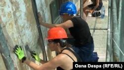 Voluntari lucrând la fațada unei case istorice în Roșia Montană