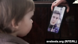 The 2-year-old daughter of imprisoned Belarusian blogger Ihar Losik looks at her father's photograph on the mobile phone of his wife, Darya Losik.