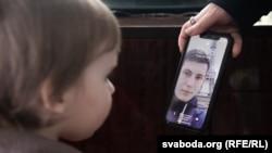 Fetița blogger-ului Iharr Losik se uită la o poză a tatălui, pe telefonul mobil al Dariei Losik, ianuarie 2021.