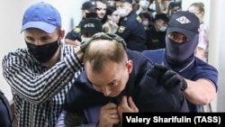 """Former Russia journalist Ivan Safronov is escorted to a hearing at a Moscow court on """"treason"""" charges earlier this week."""