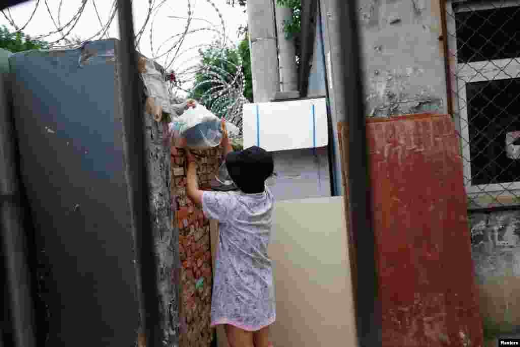 Жінка отримує їжу всередині житлового комплексу, в якому було запроваджено жорсткі заходи боротьби з вірусом та який оточили колючим дротом після нового спалаху коронавірусної хвороби (COVID-19), в районі Фенгтай, в Пекіні, Китай