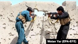 FILE: Members of the Afghan security forces take position during an operation against Taliban in Helmand province in April 2017.