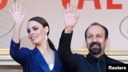 "Asghar Farhadi (right), the director of ""Le Passe,"" poses with star Berenice Bejo at the Cannes film festival in May."