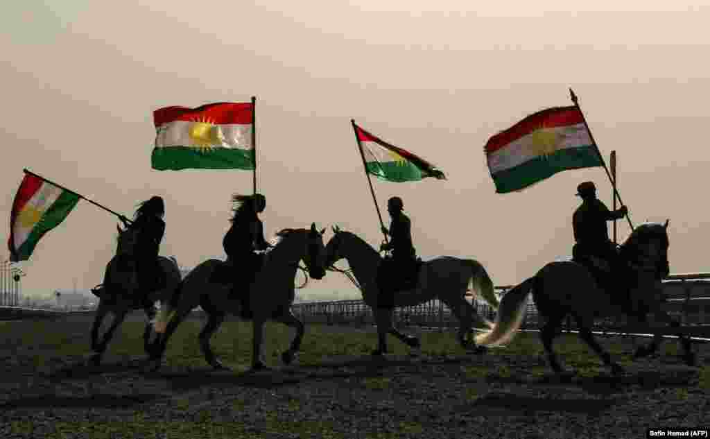 Iraqi Kurdish horsemen ride carrying Kurdish flags celebrating their flag day in the northern city of Irbil on December 17. (AFP/Safin Hamed)
