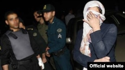 "A photo purportedly showing Hall Talayan (right, covering face), whom ""Iran"" daily said was detained on the Armenian-Iranian border on suspicion of spying."